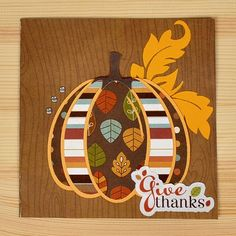 handmade Thanksgiving card ... punch art/paper pieced pumpkin ... matted ovals of patterned papers form a pumpkin ...  woodgrain stamped background  .. like it!!