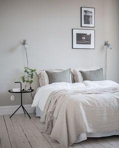deco chambre gris clair et blanc, parquet en bois clair, mur couleur grise, décoration mur de photographies en noir et blanc, table de chevet metallique noire