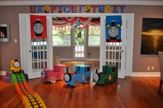 Thomas the Train party:trains made out of cardboard boxes using instructions from kevincooney.com.  James & Thomas banners made using felt. Banner from Party City. RollerCoaster is from Walmart called Step2. I added a James face and used black duct tape to make tracks.