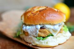 These Salmon Burgers are simply perfection! Delicious salmon patty served on an onion roll, with picked, cheese and topped with caper dill sauce!