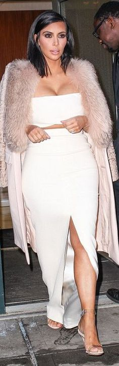 Kim Kardashian's white cropped top, clear sandals, pink coat, and slit skirt fashion id
