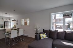Final staging done - Le Desaulniers. Open concept living room with sectional couch and green accents #pillows