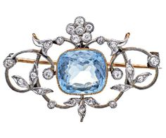 AQUAMARINE AND DIAMOND BROOCH, CIRCA 1910 Cushion shaped aquamarine, approximately 4.00 carats, within an openwork surround of foliate and scroll design highlighted with circular cut diamonds, mounted in 15ct gold and platinum.