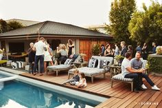 Mingling guests around backyard pool at Meritt Elliott and John Rankin's backyard dinner party