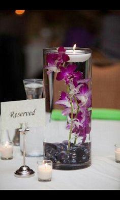 Centro de mesa con flor de orquídea dendrobium en base de cristal con piedras pulidas