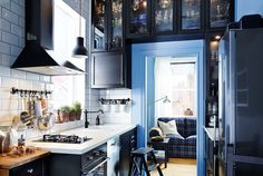 Eine schmale Küche, u. a. mit METOD Wandschrank mit Böden in Schwarz mit Front LAXARBY in Schwarzbraun, bei der die Wandschränke um den Türrahmen herum angeordnet sind