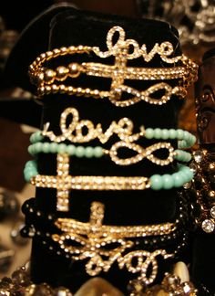 Love, crosses and infinity stacked bracelets.