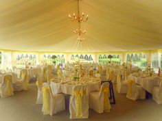 The reception marquee looks like a ray of sunshine with our yellow linings and yellow bows on the chair covers.