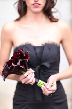Love this black dress. So unique for a wedding party dress. I also love the dark callas she's holding with it...