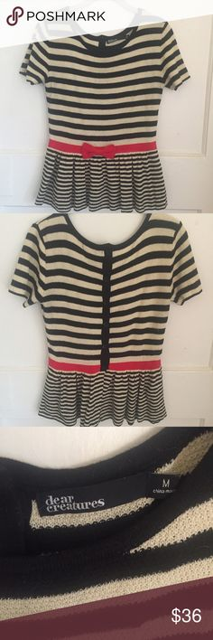 Dear Creatures Striped Knit Peplum Top Dear Creatures Striped Knit Peplum Top - size medium. Buttons down the back but is stretchy enough to pull on. Black and cream stripes with red bow. Anthropologie Tops Blouses