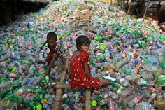 Sharmin, 13, works at a plastic recycling factory as a boy plays on a heap of bottles in Dhaka, Bangladesh on June 12, 2014. (A.M. Ahad/AP)