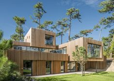A mixture of large and small windows puncture the cedar-clad facade of this house.