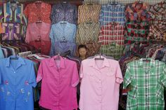 A clothing vendor bides her time as she waits for customers at her stall in Bangkok, Thailand, on July 5, 2012.