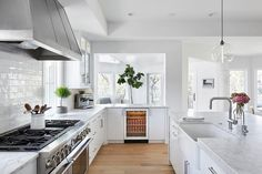 Bright, white kitchen features white flat front cabinets paired with honed gray and white marble countertops and a white glazed linear tile backsplash.