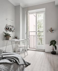 Workspace/study in bedroom: white desk, white Thonet bentwood armchair, pale limewashed floorboards, grey bed linen, French doors, indoor plants