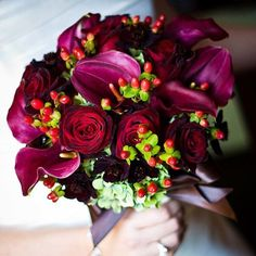 Deep Purple, Red, and Green This deep purple, red, and orange together for a color palette that is ideal for fall. Dark burgundy calla lilies and deep red roses nestled in a bed of green hydrangeas make up the main part of this pretty bouquet, and the clusters of eye-catching red hypericum berries add an unexpected accent.