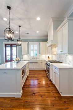 Love this kitchen! Light cabinets, backsplash, counter tops, wooden floors and a splash of blue.