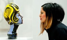 A women looks at Head with Blue Shadow, one of 125 Roy Lichtenstein works at Tate Modern. Photograph: Piero Cruciatti/Barcroft Media