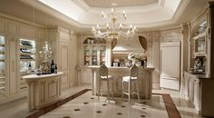 Luxury kitchen in white lacquered oak with golden decorations, granite countertop and home winery.