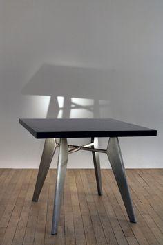 """Jean Prouvé (1901-1984) Guéridon """"Cafétéria"""", Ca. 1955 Quatre pieds en aluminium profilé supportant un plateau carré en bois lamellé plaqué de formica noir Dimensions : H. 72 x L. 87 x l. 87 cm Provenance : Société Alucam, Cameroun """"Cafétéria"""" pedestal table, Ca. 1955 Four bent steel legs with square reunited by a top made of wood with black formica Dimensions: H. 27 1/2 x L. 33 3/4 x W. 33 3/4 in. Provenance: Société Alucam, Cameroun In: Sulzer, Peter, Jean ProuveŒuvre com..."""