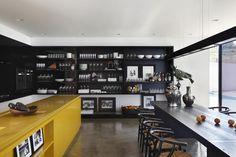 Londrina, Brasile La cucina e la zona pranzo sono caratterizzate dal contrasto tra colori forti: il giallo del bancone ravviva il nero della libreria e del tavolo Foto di Denilson Machado (MCA Estúdio)