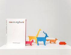 """Às vezes deparamo-nos com algo que é tão simples, mas tão brilhante, que nos questionamos como não vimos nada assim antes. É o caso do livro de Sunkyung Kim, """"Zoo In My Hand"""", um livro de actividades para crianças, absolutamente delicioso. Contém 40 páginas de papel colorido, cada uma com um desenho de um animal e sua descrição em 6 idiomas, pronto a cortar.  Tudo o que precisa é um par de tesouras, seguir a linha pontilhada e dobrar segundo a indicação. Com uns lápis de cor, a diversão é…"""