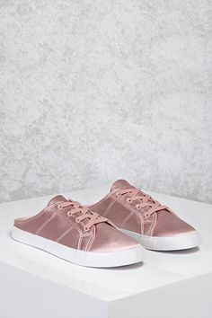 A pair of satin sneakers featuring a backless slip-on design, contrast sole, and a lace-up top.