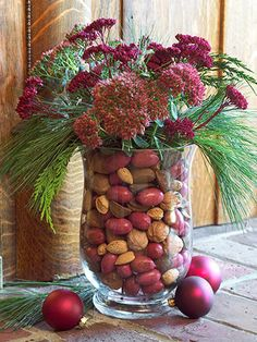Tuck a small vase inside a larger glass urn and fill the space between the two with mixed nuts. Fill the small vase with water and add fresh flowers or greenery. Replace nuts with shells?