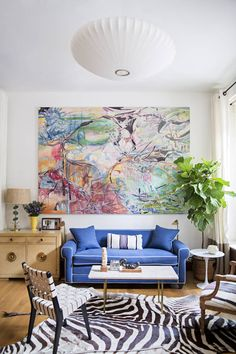 pops of color- cowhide rug- and a bright abstract painting - domino.com