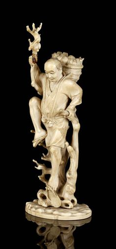 A Japanese carved ivory okimono, Meiji period Depicting a man climbing a tree, with a basket on his back, 18cm, signed to a red tablet