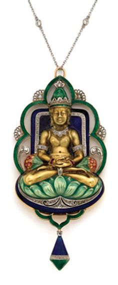 *Gold, Platinum, Enamel and Diamond Buddha Pendant with Platinum and Diamond Chain, Circa 1920.  The gold buddha, seated cross legged on a green enamel cushion, arms folded in his lap, accented by ruby bracelets and diamond arm bands, his neck draped in a diamond necklace, his head topped by a green enamel and diamond crown, seated in front of a deep blue enamel background, enclosed by a scalloped green enamel and diamond frame, suspending a blue and green enamel and diamond pendant.