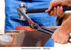 Red hot iron being hammered into shape on an anvil.
