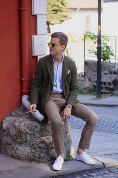 Shop this look on Lookastic:  http://lookastic.com/men/looks/sunglasses-long-sleeve-shirt-pocket-square-double-breasted-blazer-chinos-low-top-sneakers/9358  — Yellow Sunglasses  — Light Blue Long Sleeve Shirt  — Blue Print Pocket Square  — Dark Green Double Breasted Blazer  — Brown Chinos  — White Low Top Sneakers