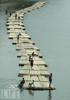 Children play on rafts of bamboo being transported along the river Gomati in Udaipur.