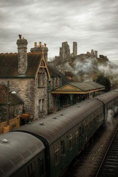 An English railway station in the days of steam. Corfe Castle in the background (Kirrin Castle in the famous five).