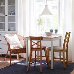 Mesa de refeição com tampo com acabamento envelhecido e pernas em branco, com diferentes cadeiras de madeira