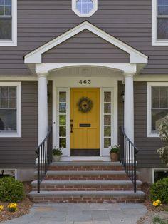 yellow door, white trim, dark gray siding, brick steps
