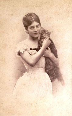 Portrait of a woman holding a disgruntled cat, ca. 1880-1890.