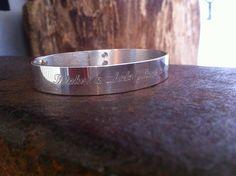 Zilveren armband met een gegraveerde tekst.