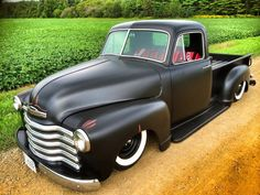Chevy chevrolet advanced design pickup truck slammed in the weeds laid out on black steel wheels wrapped in wide white wall tires and trimmed with a mexican blanket interior and a satin black flat back paint job