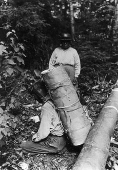 George L. Waite photo of an Ojibwa man who has a pack of birch bark on his back…