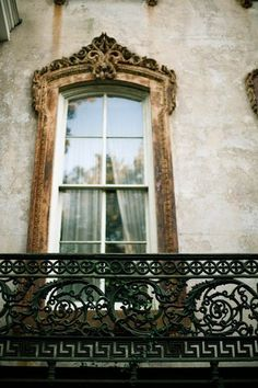 A window with a gilded Baroque frame and an ornate wrought iron balcony railing grace this building in Paris  (via Marcus Design)