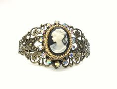Elegant cameo cuff bracelet with vintage cameo setting, filigree cuff, embellished bracelet with lady profile cameo.  Made in Tennessee, USA.    One of a kind jewelry created in my home studio near Chattanooga, TN.  This bracelet will be shipped via USPS Priority mail.    Understated elegance is the best way to describe this cuff bracelet.  I started with an antiqued brass/bronze filigree cuff.  Next, I have used a faux black and cream cameo which I placed into a vintage antiqued gold…