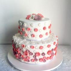 Um bolo delicado para uma mulher muito delicada. Dezenas de flores de açúcar em tons rosa, lilás escuro e branco decoraram este bolo de aniversário. Massa de baunilha e recheios de nozes com doce de leite, ameixas pretas e creme de baunilha no bolo maior. Massa de chocolate e recheios de brigadeiro branco e ganache no bolo menor.