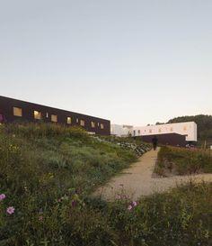 Construído na 2014 na Pont-sur-Yonne, França. Imagens do David Romero-Uzeda. O edifício se integra na paisagem de Pont-sur-Yonne. Os blocos escuros abrigam os 96 dormitórios. A entrada principal está ao redor de um pátioque...