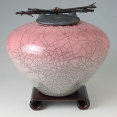 Raku Ceramic Cremation Urn Standard size w/ wood stand 10.75″W X 9.5″T; room for 220 cubic inches of cremains John Dodero has developed a specialty in high quality cremation urns for ashes. Secure flange lid stays put unless turned upside down; includes sealable poly liner bag for extra security. Adorned with black bamboo & Zuni inspired gemstone bear fetish held in place w/ sinew; there is ample sinew on the underside of the lid to tie a special parting wish. Available in 7 sizes and 15…