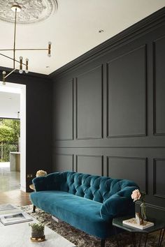 Sofa upholstered in teal velvet contrasts with dark grey painted wood panelling. Interior Photography of Wandsworth home, by London Architectural and Interiors photographer, Matt Clayton