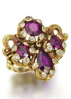 An art nouveau ruby and diamond cluster ring, attributed to Marcus & Co, circa 1900. Of quatrefoil design, the pear-shaped and circular-cut rubies within a chased serpentine surround with old brilliant-cut diamond detail, between pierced scrolling shoulders.