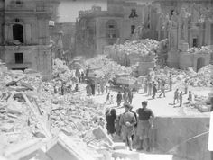 APR 15 1942 Malta awarded the George Cross Valetta bomb damage A heavily bomb-damaged street in Valletta, Malta. This street is Kingsway, the principle street in Valletta. Service personnel and civilians are present clearing up the debris.
