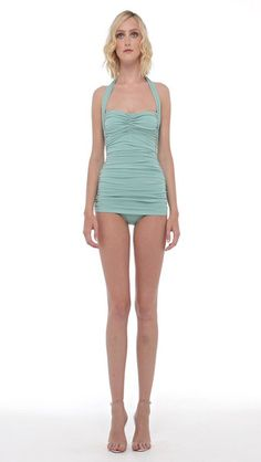 This one piece wonder is a Norma Kamali classic. The Bill has a sweetheart neckline and halter strap that curves comfortably across the shoulders behind the neck. It is constructed with a nylon-lycra base that provides flexible form. Draped across the body is a second top layer, a figure-flattering stretch polyester-jersey blend that cinches at the sides with ruching throughout. Pair with the Shirred Skirt to Mid-Calf.